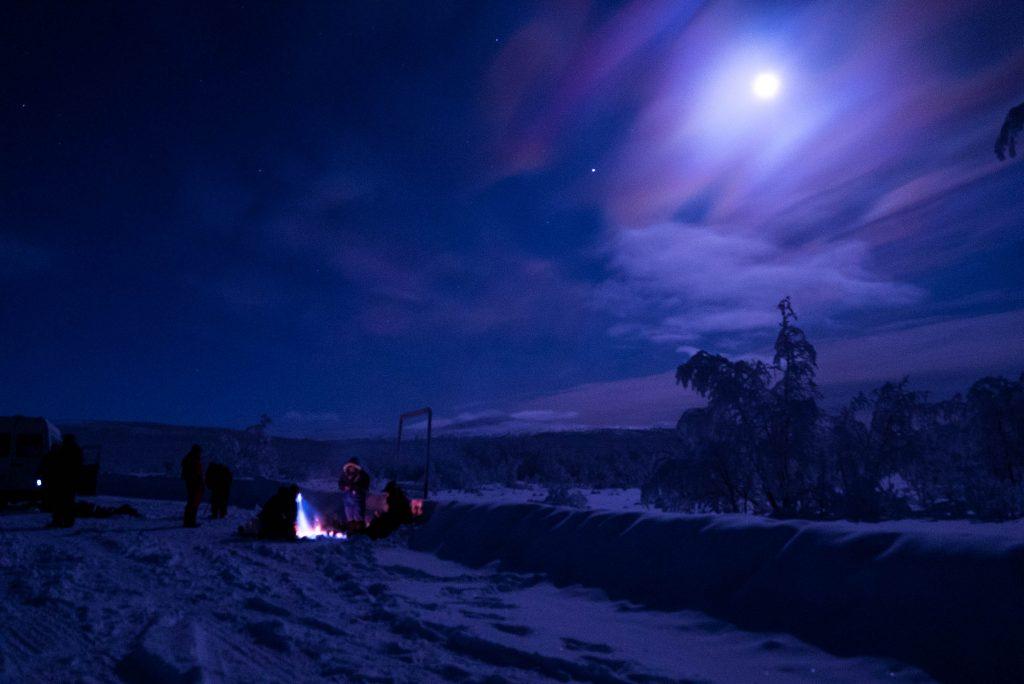 Kampvuur in een besneeuwd landschap bij maanlicht