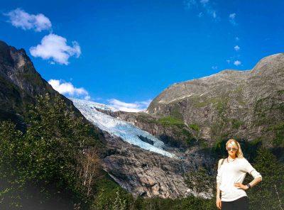 Vrouw poseert voor Boyabreen gletsjer in Noorwegen