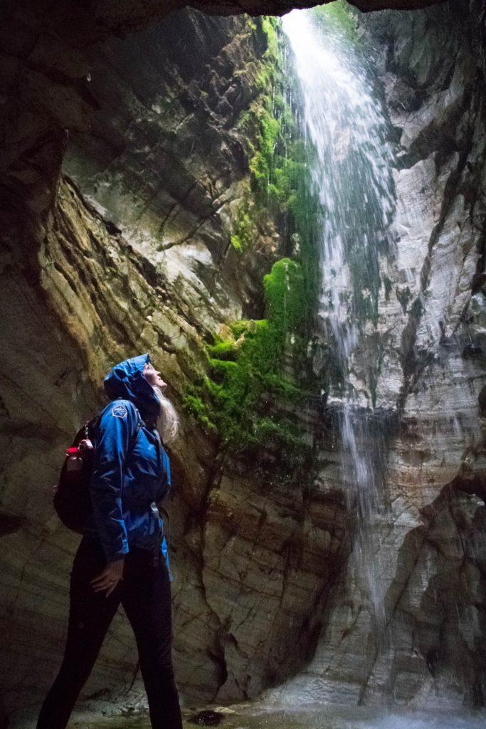 Vrouw poseert bij waterval in Trollkirka grotten Noorwegen