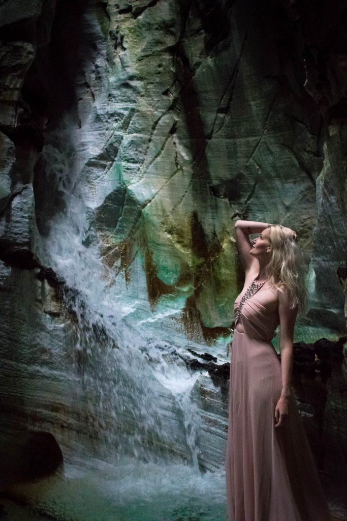 Vrouw poseert bij waterval in Trollkirka grot Noorwegen