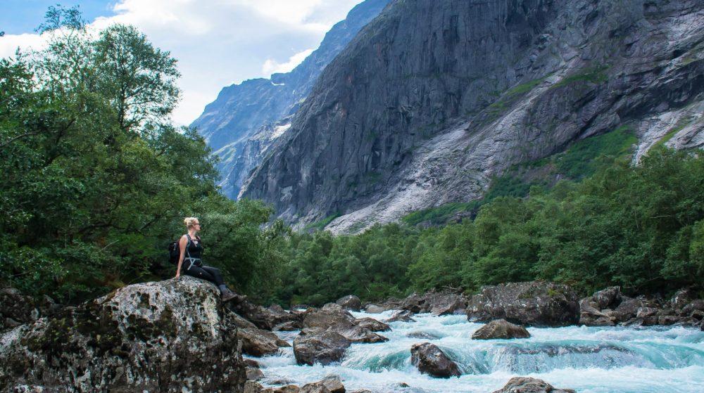 Vrouw zit op steen langs Eiafossen, Rauma