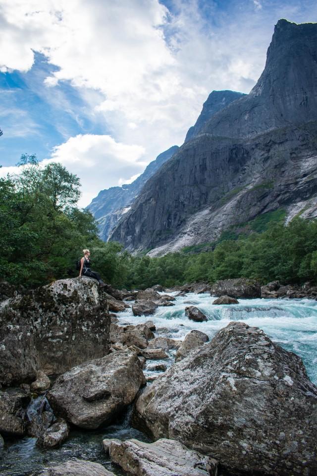 Vrouw zit op rots onder Trollveggen en langs de Rauma rivier