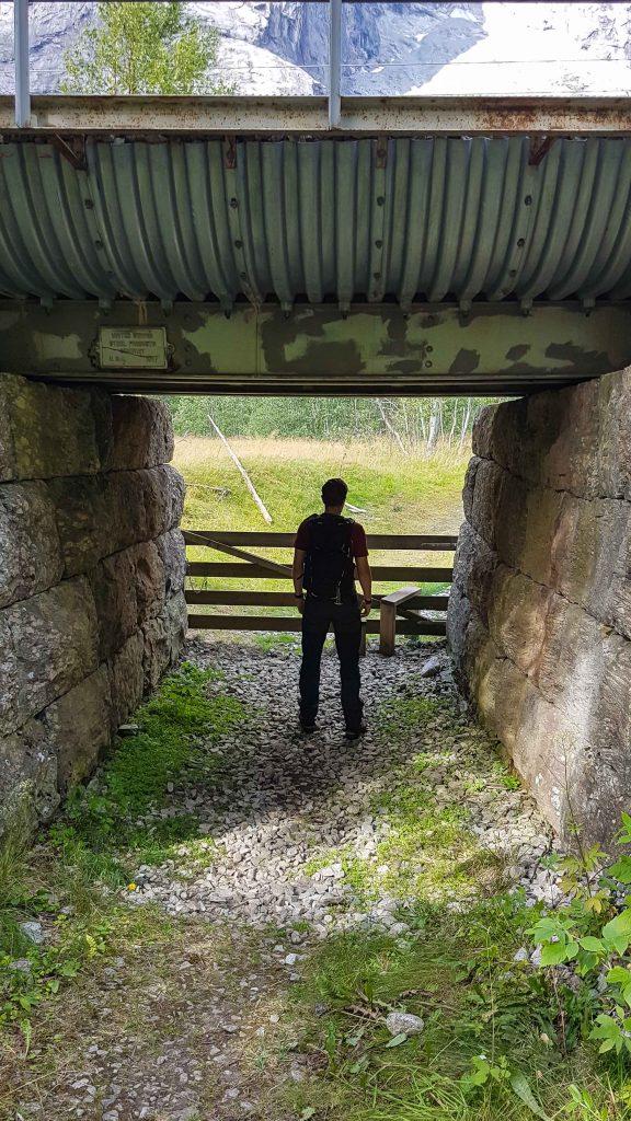 Een man poseert onder het viaduct naar Eiafossen wandeling
