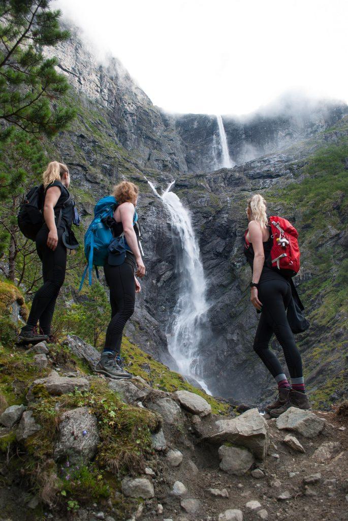 Drie vriendinnen poseren voor de Mardalsfossen waterval in Noorwegen