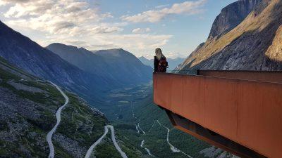 Vrouw met rugzak op het Trollstigen uitkijkpunt bij zonsondergang