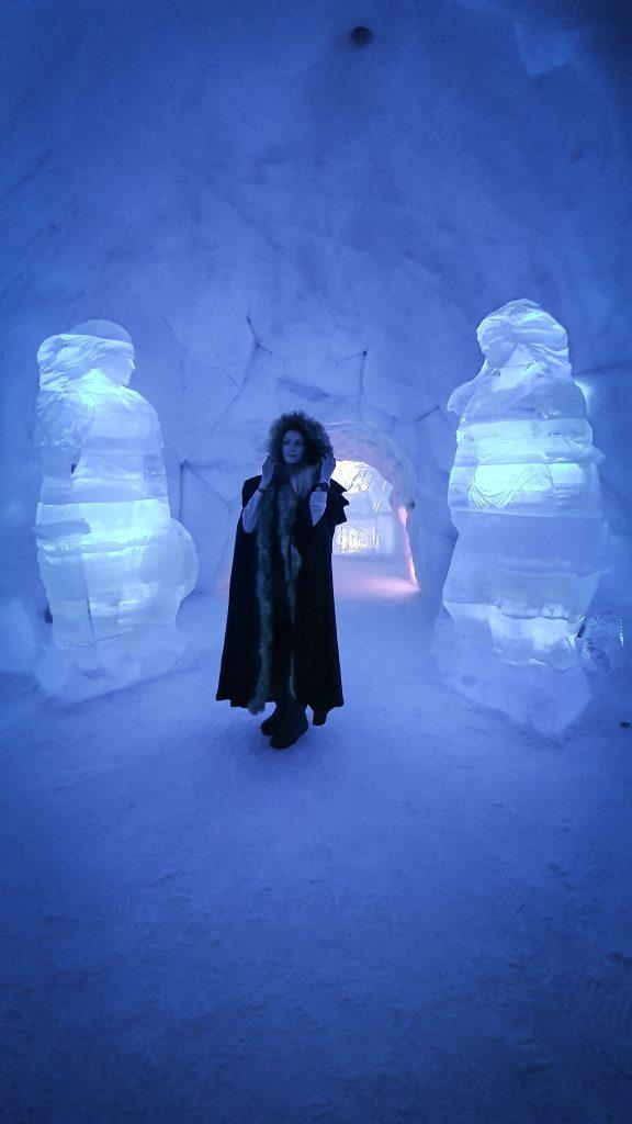 Vrouw in cape tussen shield maidens van ijs in Tromsø Ice Domes