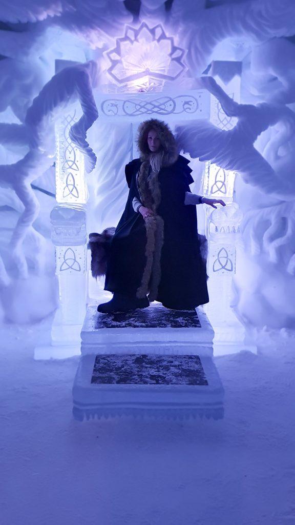 Vrouw in cape op troon van ijs in Tromsø Ice Domes
