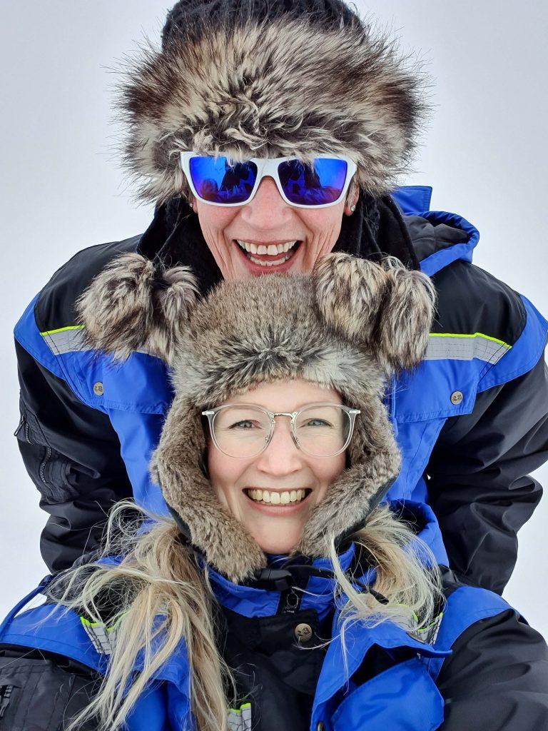 Lachende moeder en dochter op hondenslee bij Tromsø Ice Domes